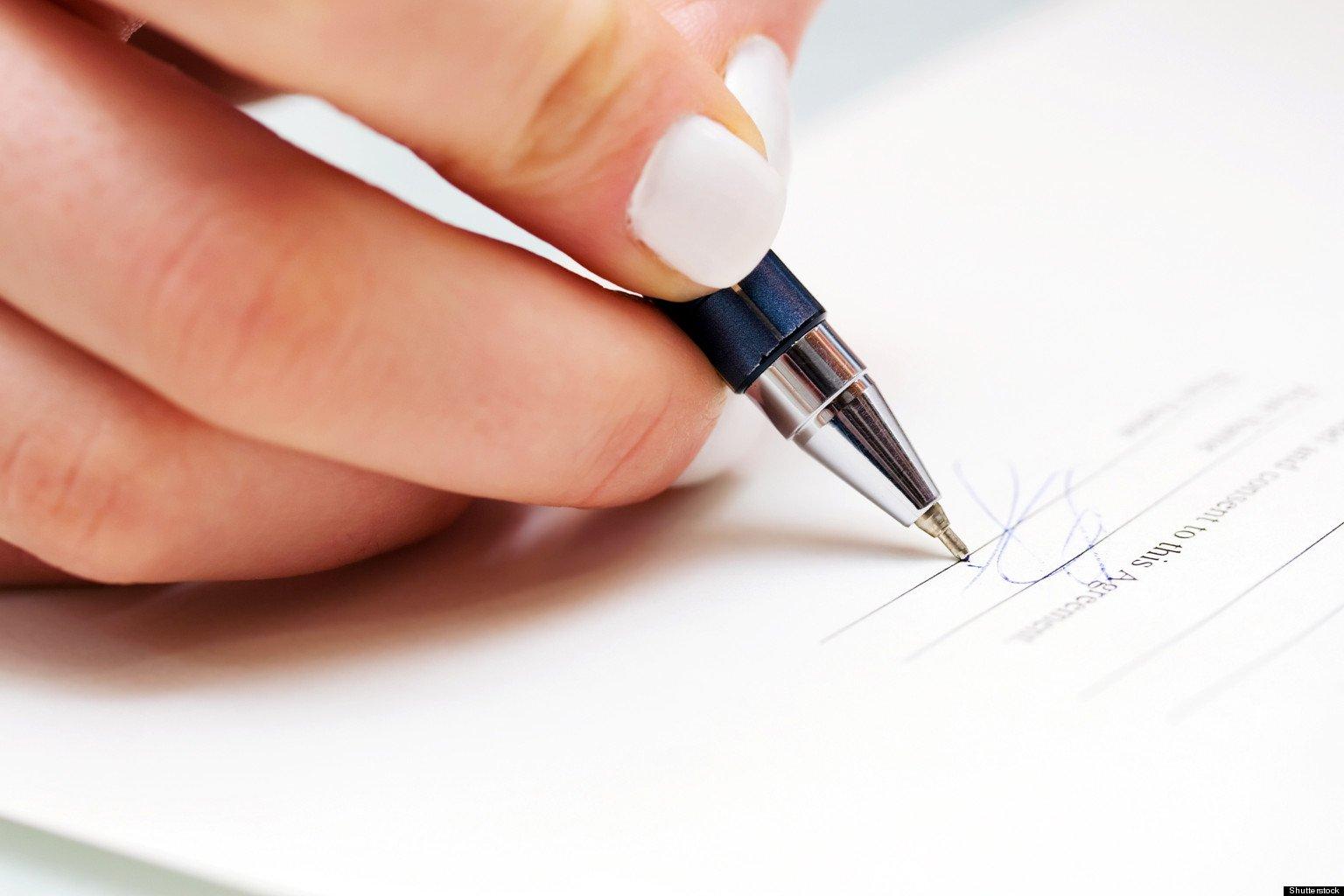 Woman writing signature on document